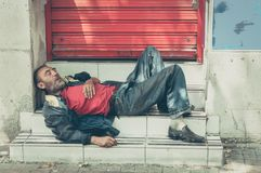Poor homeless man or refugee sleeping on the stairs on the street, social documentary concept. Homeless man. Poor homeless man or refugee sleeping on the stairs royalty free stock images