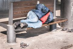 Poor homeless man or refugee sleeping on the wooden bench on the urban street in the city, social documentary concept.  stock photo