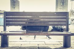 Poor homeless man or refugee sleeping on the wooden bench on the urban street in the city, social documentary concept.  stock photography