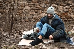 Poor homeless man sitting on cardboard. In city park royalty free stock photos