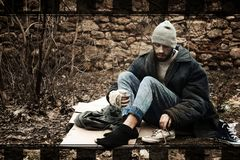 Poor homeless man sitting on cardboard in park. Poor homeless man sitting on cardboard in city park royalty free stock image
