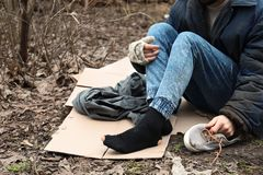 Poor homeless man sitting on ground outdoors. Closeup royalty free stock image