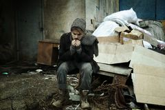 Poor homeless man sitting near rubbish. At dump royalty free stock photography