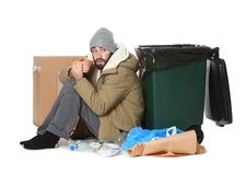 Poor homeless man sitting near trash bin. Isolated on white stock photography