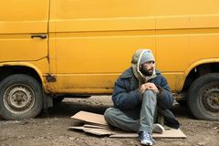 Poor homeless man sitting near van. Outdoors royalty free stock photos