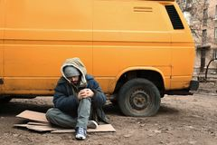 Poor homeless man sitting near van. Outdoors stock images