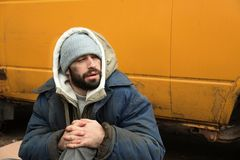 Poor homeless man sitting near van. Outdoors royalty free stock image