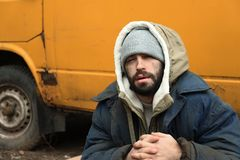 Poor homeless man sitting near van. Outdoors stock photography