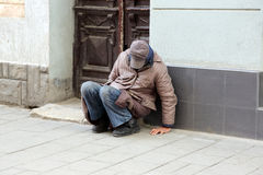 Poor homeless man sitting near the wall of the building Royalty Free Stock Photos