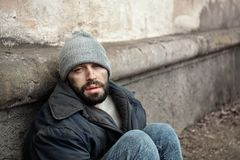 Poor homeless man sitting near wall on street. Space. For text royalty free stock photos