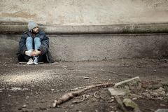 Poor homeless man sitting near wall on street. Space for text stock photo