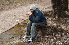 Poor homeless man sitting on stump. Outdoors stock photo