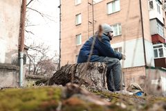 Poor homeless man sitting on stump. Outdoors stock images