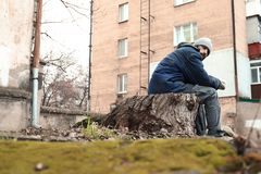 Poor homeless man sitting on stump. Outdoors royalty free stock images