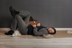 Poor homeless man sleeping on floor. Near dark wall royalty free stock photo