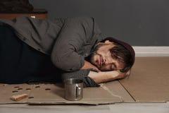 Poor homeless man sleeping on floor. Near dark wall stock image