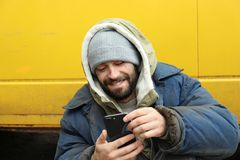 Poor homeless man with stolen smartphone. Outdoors royalty free stock photography