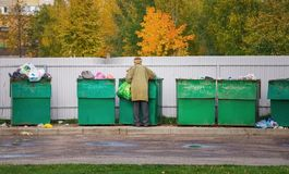 Poor homeless old man searching in garbage Royalty Free Stock Images