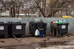 Poor homeless people collect bottles near trash cans. Dummographic problems of humanity royalty free stock photos