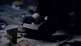 Poor homeless person sitting on ground reading bible, praying for better life stock photo