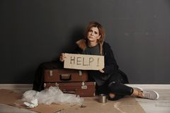 Poor homeless woman asking for help. On floor near dark wall royalty free stock photo
