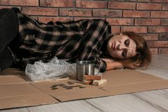 Poor homeless woman lying on floor. Near brick wall royalty free stock images