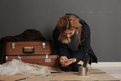 Poor homeless woman with suitcase counting coins. On floor near dark wall royalty free stock images