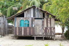 Poor House with Solar Panel. Poor wooden house in remote coastal area with a solar panel as the electricity source, Saporkren Village, Raja Ampat, West Papua Royalty Free Stock Image