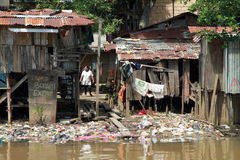 Poor houses. With lots of trash on a bank of a river in Sorong in Indonesia Royalty Free Stock Photo