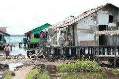 Poor houses by the sea. Poor houses with people on a bank of a sea in Sorong in Indonesia Stock Photo