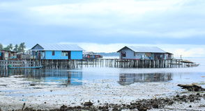 Poor Houses on the Sea Water. Portrait of poor houses at low tide inhabited by the fisherman and their family in Sorong, West Papua, Indonesia. These houses Royalty Free Stock Photo