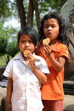 Poor and Hungry Children. Portrait of poor and hungry children eating biscuits at Cambodia Stock Photos