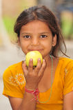 Poor hungry girl. Poor girl child eating apple royalty free stock photos