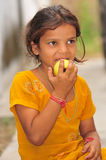 Poor hungry girl. Poor girl child eating apple Stock Images