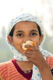 Poor hungry girl. Poor girl child eating orange Stock Image