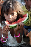 Poor Hungry Indian Girl. A poor Indian beggar girl hungrily eating a watermelon Royalty Free Stock Photography