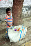 Poor Indian Boy. A poor Indian boy stands with a huge bag containing Indian flags to be sold on the 64th Independence day Royalty Free Stock Photo