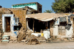 Poor indian family house with broken walls on dirty street Stock Photography