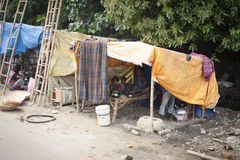 Poor Indian family living in a makeshift shack by the side of the road. VARANASI, INDIA - OCTOBER 28, 2014 : Poor Indian family living in a makeshift shack by Stock Photo