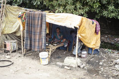 Poor Indian family living in a makeshift. VARANASI, INDIA - OCTOBER 28, 2014 : Poor Indian family living in a makeshift shack by the side of the road Stock Photo