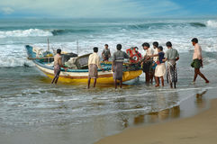Poor Indian fishermen pushed the boat for water, Orissa, India Royalty Free Stock Photos