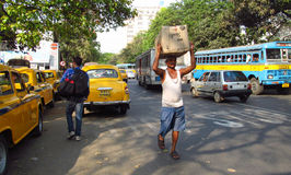 Poor indian man carrying a box on his head on the street of Kolkata Royalty Free Stock Photo