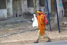 Poor indian man in traditional orange clothes begging for the money on the street Royalty Free Stock Images