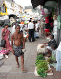 Poor indian man walking. In sari on a busy the street Stock Images