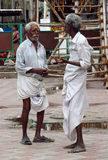 Poor indian men in traditional sarong clothes talking on the street Royalty Free Stock Images