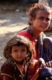 A poor Indian Mother  with her daughter. Pushkar, India: A poor Indian Mother  with her daughter, sit on the street in Pushkar Royalty Free Stock Image