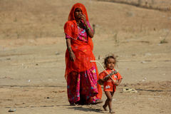 A poor Indian Mother with her son. Pushkar, India: A poor Indian Mother orange dressed with her son, standing on the sand in Pushkar Stock Photography
