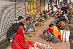 Poor indian people eating free food at the street in Varanasi, India Royalty Free Stock Images