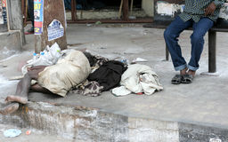 :Poor Indian senior man sleep in a Bus stop on a busy road Stock Photos