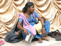 Poor indian woman. Poor people sit outside the temples and religious places seeking  help.They also watch the footwear left outside by the devotees for money Royalty Free Stock Image